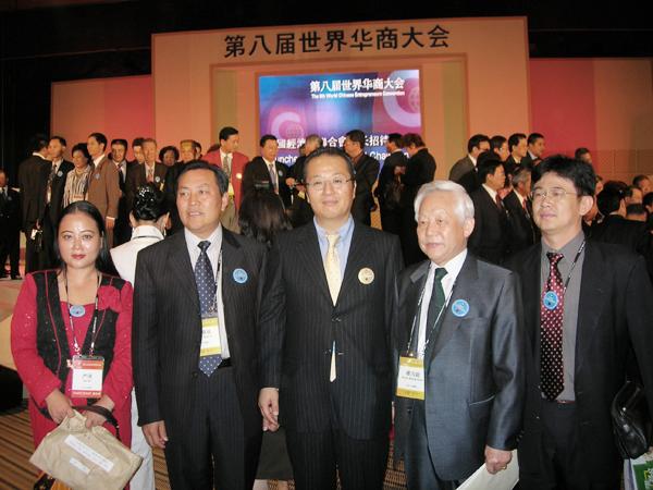 在第八届华商会上严琦董事长与华商会主席(中)及会议代表合影