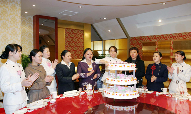2008年3月8日,全国政协委员严琦与女员工一起欢庆三八妇女节